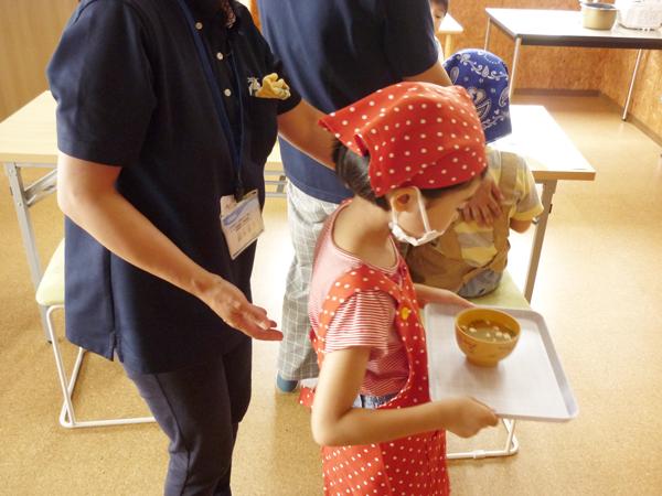 熱いお味噌汁を慎重に配膳する小学生の様子