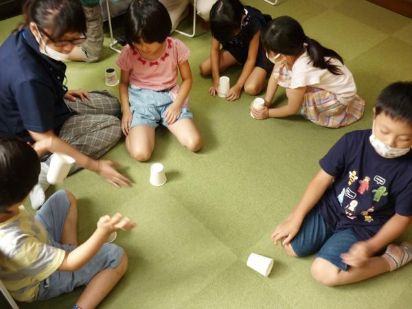 児童が紙コップで遊ぶ様子